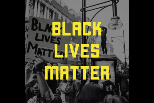 "Black and white image of protestors. Yellow text overlay reads ""Black Lives Matter"""