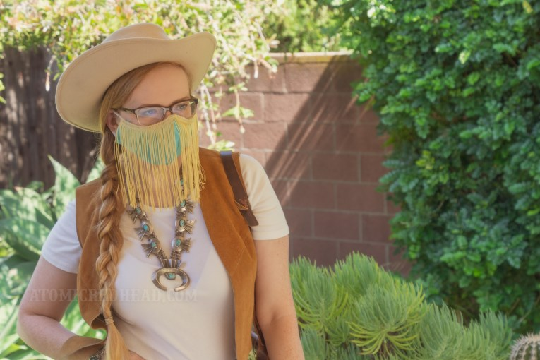 Myself, standing in my backyard, wearing a cream cowboy hat, a turquoise colored mask with gold fringe hanging from the top, a white t-shirt with a caramel colored suede vest over, a large turquoise squash blossom, and white and maroon plaid bell bottoms.