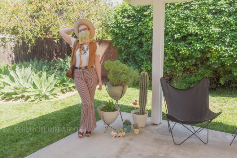 Myself, standing in my backyard, wearing a cream cowboy hat, a turquoise colored mask with gold fringe hanging from the top, a white t-shirt with a caramel colored suede vest over, a large turquoise squash blossom, and white and maroon plaid bell bottoms. Various planted cacti are visible on the right.