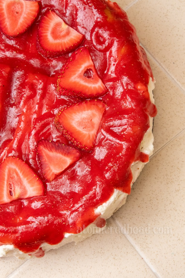 Red strawberry glaze on white cheesecake, with sliced strawberries placed on top.