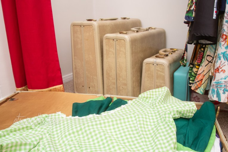 A green and white gingham dress sits in an open suitcase, with matching suitcases behind it sitting on the floor of my closet.