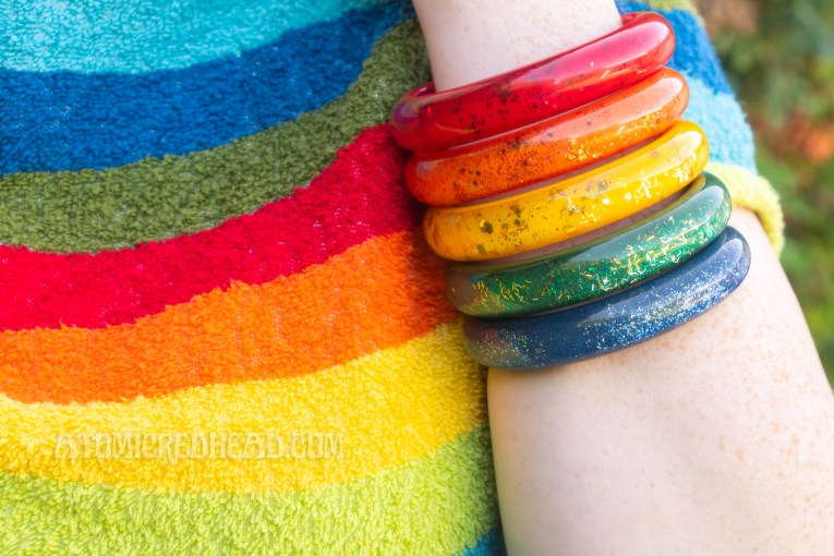 Close-up of bracelets against my rainbow shirt.
