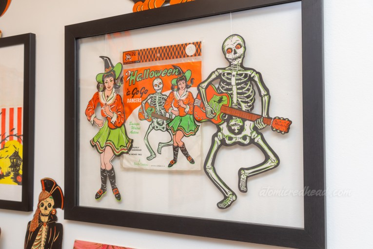 Two diecut Halloween decorations hang in a frame, an attractive witch in an orange top and green mini skirt appears to dance, and a skeleton plays an orange and green guitar.
