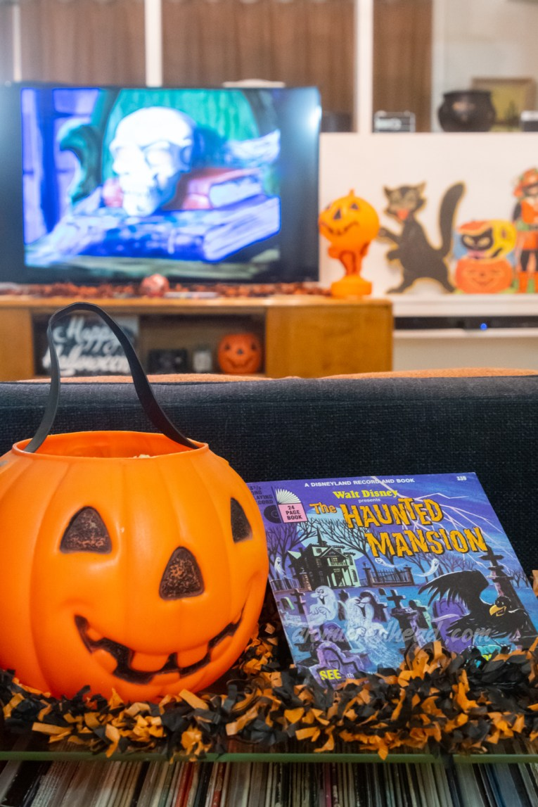 A jack o'lantern trick or tree bucket sits next to the record for the Haunted Mansion, in the background an animated skull is on the TV.