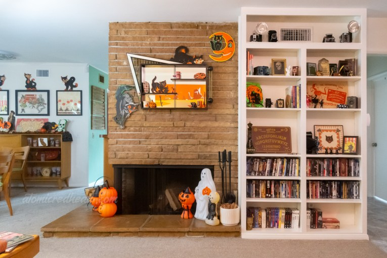 Overall view of the fireplace with a built in bookcase to the right. Various Halloween decorations scatter the shelves.