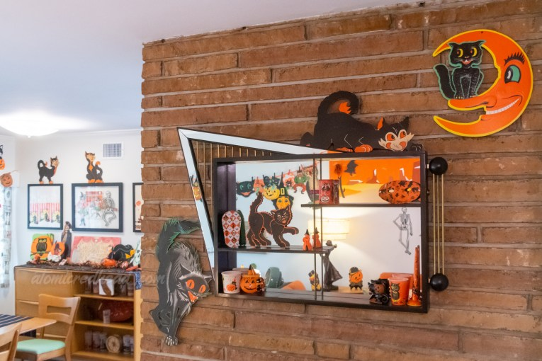 A mirrored shadow box hangs above the fireplace. Around it are two black cats, and another black cat that sits in the moon. Inside is another paper black cat, several noise makers, and an orange mask with a design of cats, pumpkins and ghosts.