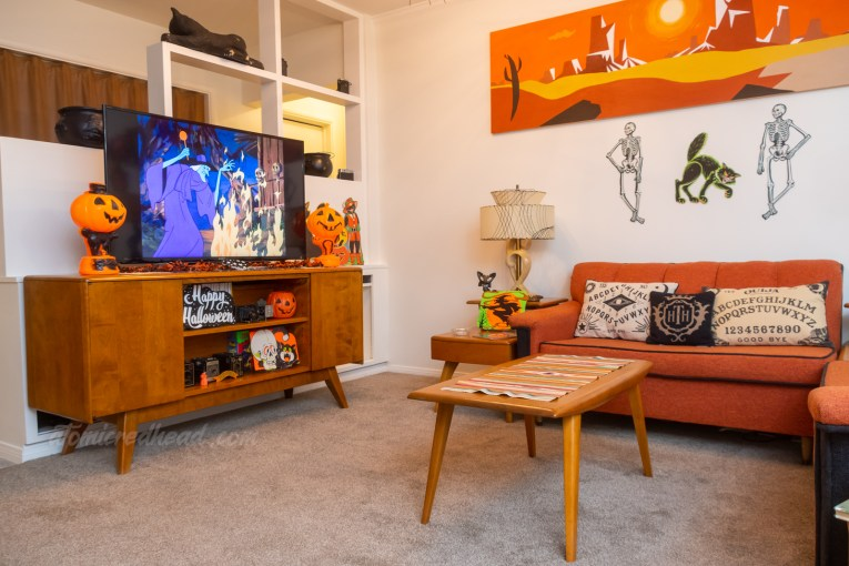A view of our living room. A cartoon witch appears on the TV. The TV is flanked by two blow mold plastic pumpkin. Various Halloween decorations are scattered throughout.