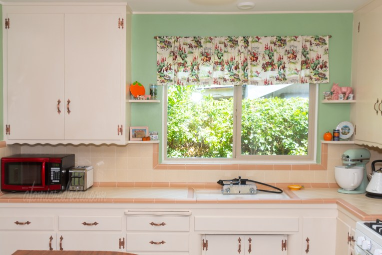 Direct view toward the sink. On either side of the window above the sink are small shelves which have various vintage orange and California souvenirs on them.