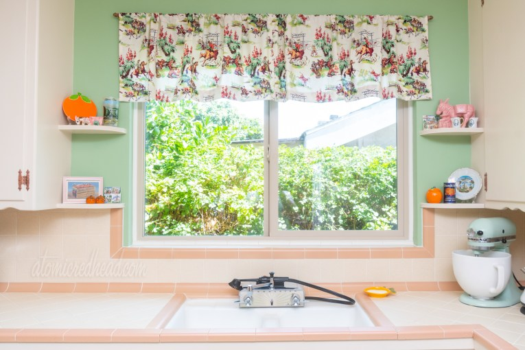 Direct view of sink. Outside the window is a green hedge. Above the window is a cream valance with images of cowboys roping steer, riding horses, and around a campfire. The fabric design is made up of pinks, browns, and greens, similar in shade to the walls.