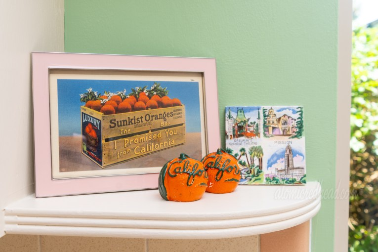 "Close-up of one shelf near the sink. Orange shaped salt and pepper shakers, which read ""California"" in green script across them, a framed postcard features a crate of oranges, on the side of the crate reads ""Sunkist Oranges - the box I promised you from California,"" and a tile featuring Grauman's Chinese Theatre, a mission, palm trees, and LA City Hall."