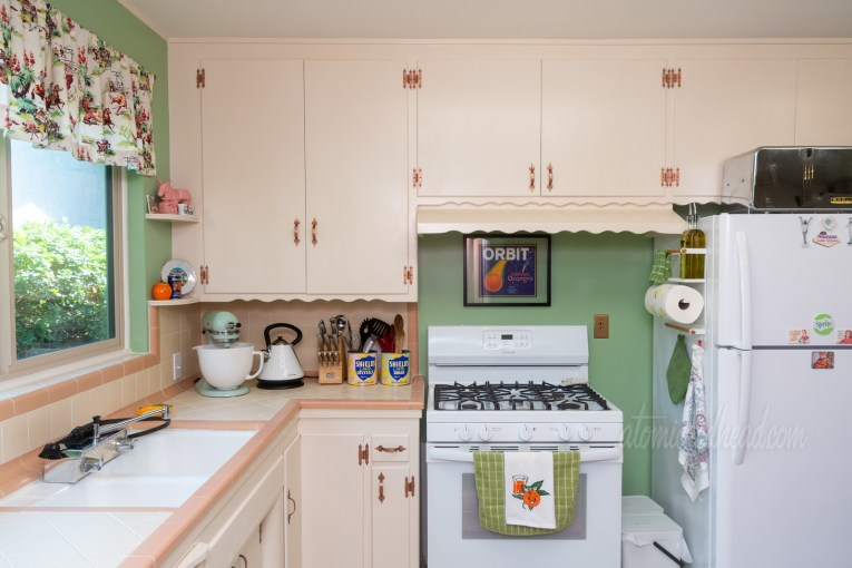 "A view toward the stove, which is tucked under cream cabinets and against a green wall. Above the stove hangs a vintage fruit crate label that has an orange streaking across the sky like a comet, and above it reads ""Orbit"" in large white letters. Hanging on the handle of the stove is a white towel with an orange with a face o it."