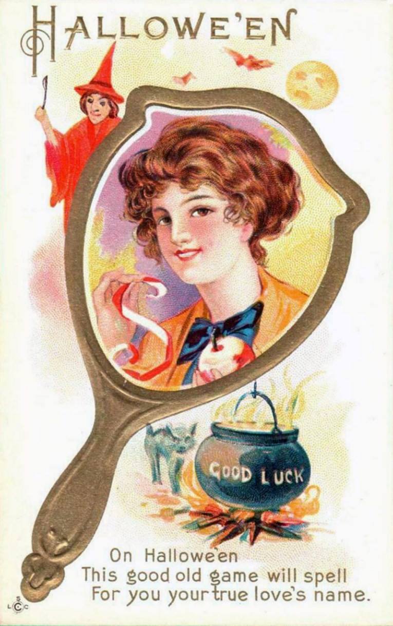 "A woman's face appears in a hand mirror, she holds an apple and apple peel. A small witch peeks out from the upper left, a cauldron sits in the lower right, with text reading ""Good Luck"" on it. Text along the top of the postcard reads ""Halloween."" Text at the bottom of the postcard reads ""On Halloween This good game will spell For you your true love's name."""