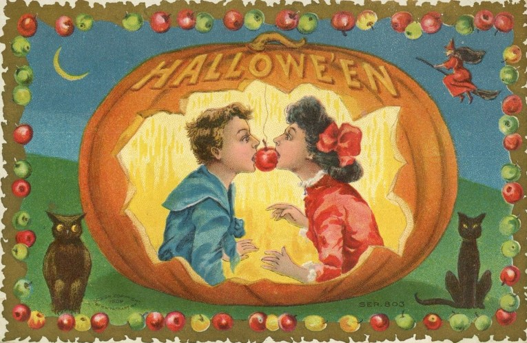 "A boy and girl bite into the same apple inside a pumpkin. Text at the top reads ""Halloween."""