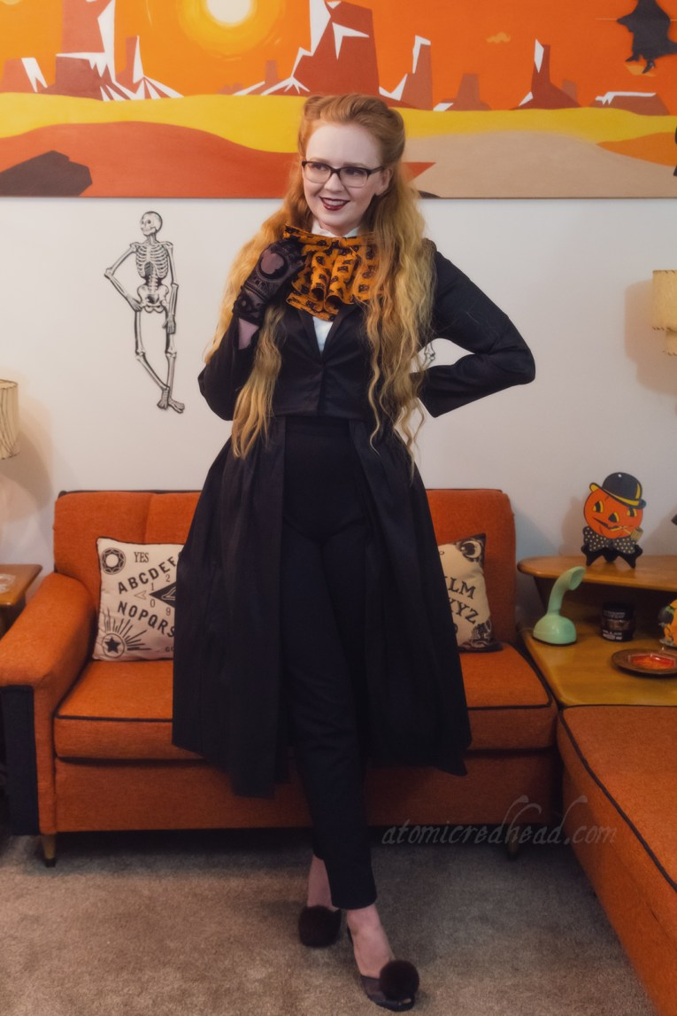 Myself wearing a black top that features an open skirt, with black cigarette pants underneath. A white blouse peeks out at the top and a large orange bow with a print of black cats is worn at the neck.