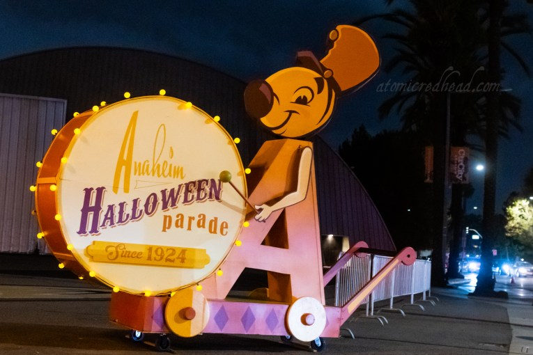 "Float of the Anaheim mascot, Andy Anaheim, dressed as a marching band member banging a large drum. The drum reads ""Anaheim Halloween Parade Since 1924."""