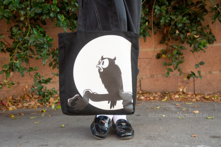 Close-up of my purse, a black and white image of an owl sitting on a branch against a full moon.