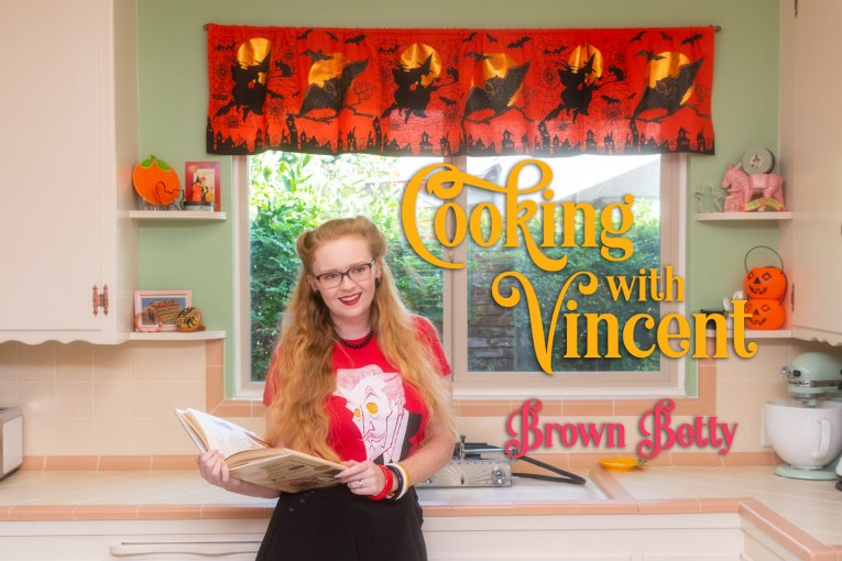 """Myself, wearing a red shirt with an illustration of Vincent Price on it, holding a cookbook, standing in front of the sink in our kitchen. An orange valance hangs above the window, and features witches an owls. Shelves that flank the window have small pumpkins, a ghost, and cauldron. Text overlay reads """"Cooking with Vincent Brown Betty"""""""