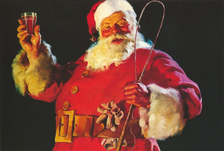 Santa in his red suit, with his cap on his head, holds a glass of Coke in one hand and a whip in the other.