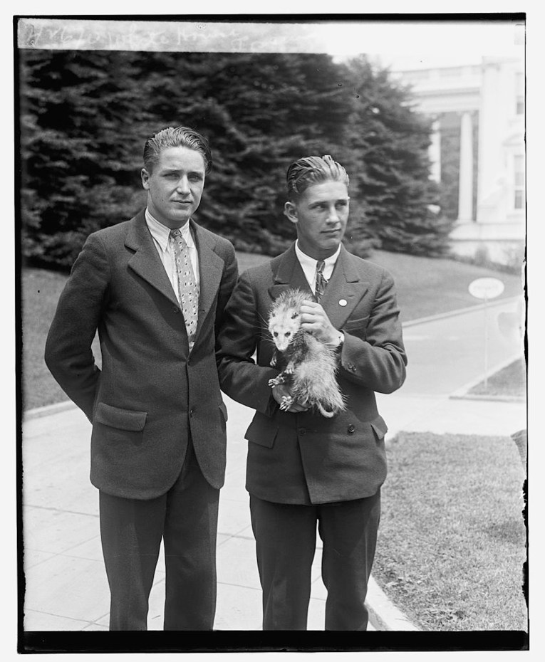 Two men in suits stand on the lawn of the White House, one holds an opossum.