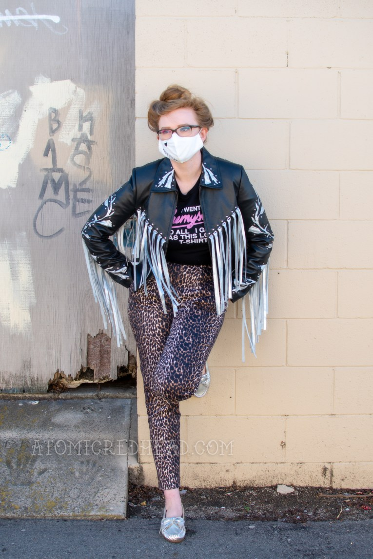 "Myself wearing a black and silver fringe leather jacket, black tee, and leopard print pants. I also wear a white face mask that has embroidered details of a heart and the word ""rotten"" that emulates Harley Quinn's face tattoos."