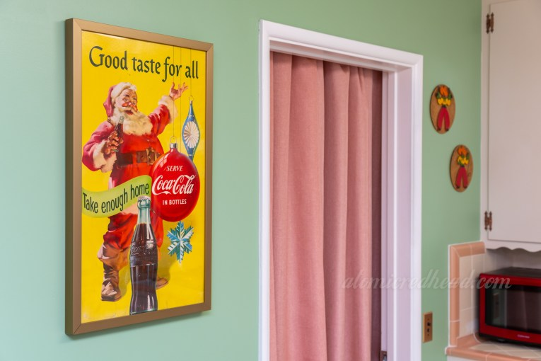 "A framed Coca-Cola advertisement featuring Santa reading ""Good taste for all"" hangs on our kitchen wall."