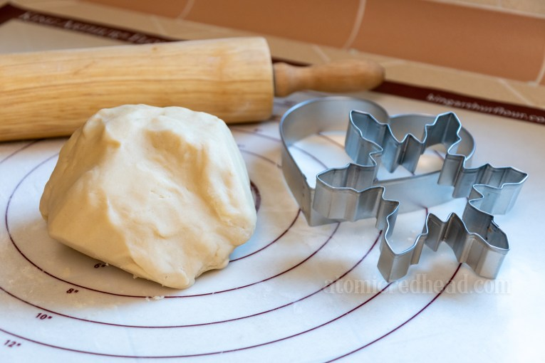 A large ball of dough sits on a mat, next to it a rolling pin, and two cookie cutters, a heart and snowflake