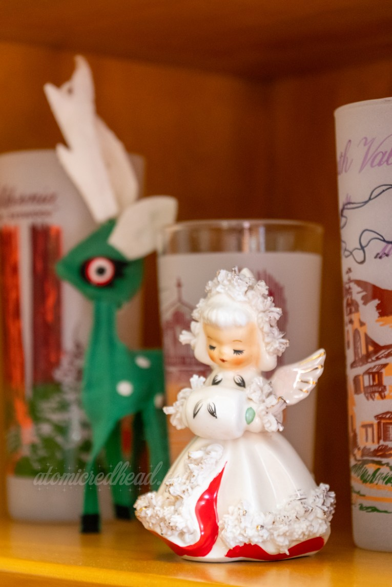 A small ceramic figure of an angel in a white gown with hood, she has her hands in a small white muff. Behind her is a small green reindeer.