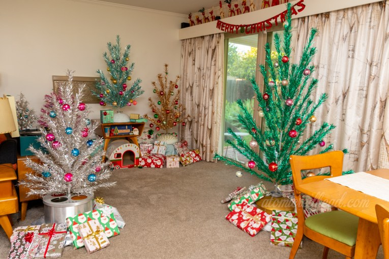 """View of our """"aluminum forest"""" a 3 three silver tree, 3 foot pink tree, 3 foot blue tree, 3 foot gold tree, and 6 foot green tree."""