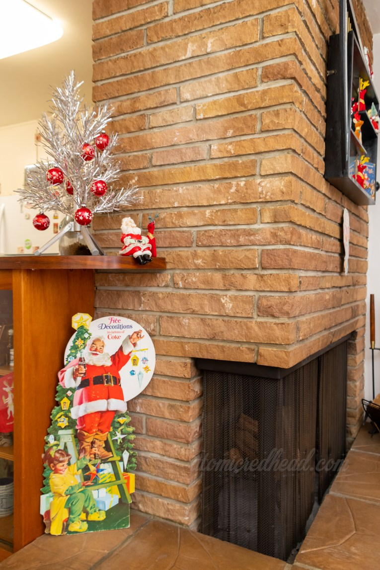 A built in bar meets our brick fireplace. On top of the bar is a short silver aluminum tree with small red ornaments on it. Below it is a cardboard standee advertising Coca-Cola, featuring Santa Claus.