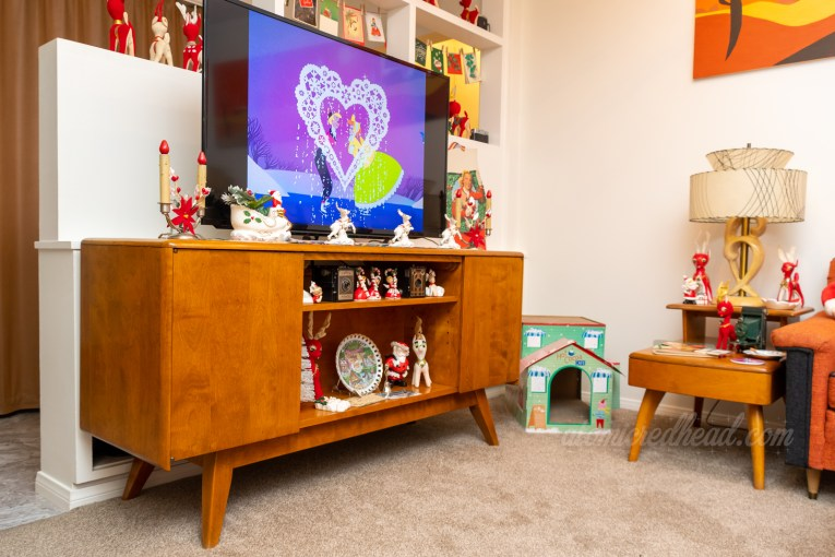 Our entertainment center. On the TV a couple on ice skates leans in for a kiss, a scene from the short Once Upon a Wintertime. A ceramic Santa and reindeer sit in front of the TV. Various Christmas decorations scatter the shelf below.