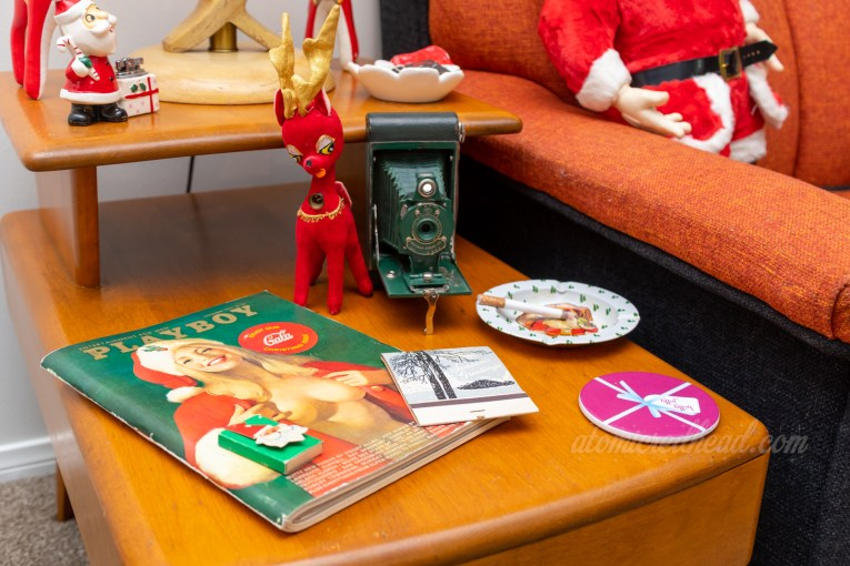 A vintage issue of Playboy features a blond woman in a Santa costume. Next to her is an ashtray featuring Santa.