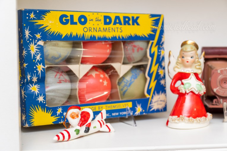 Close-up of one of our shelves, which features a box of glow in the dark ornaments, the box has stars on it. In front of it sits a small ceramic Santa on a rocket. to the right is a small angel in a red dress holding a star.