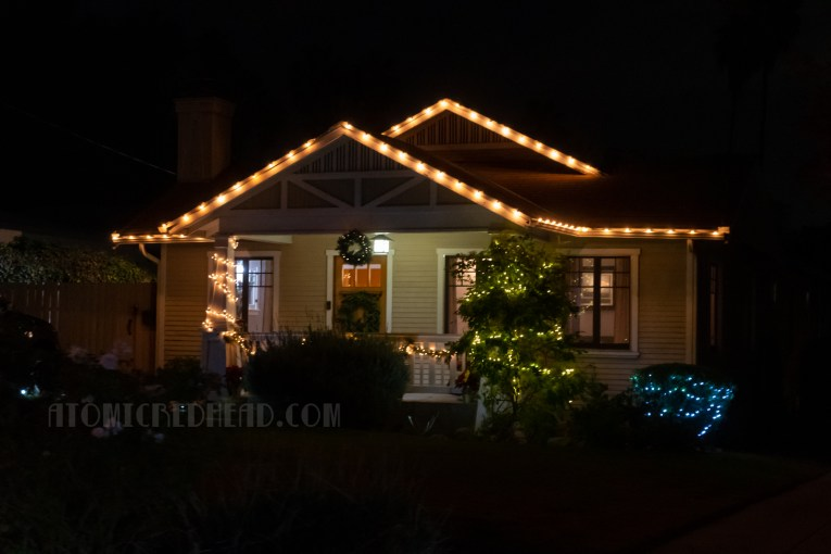 A small bungalow has white lights along its roof line.