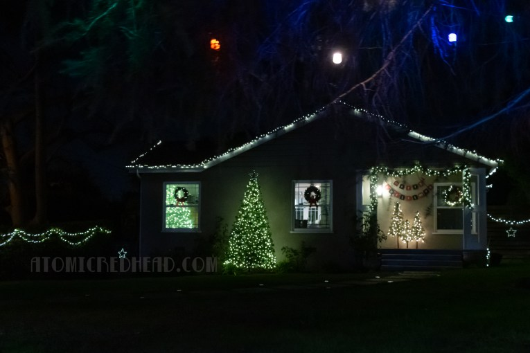 A small home decorated with white lights on its roof, and Christmas wreaths in the window.
