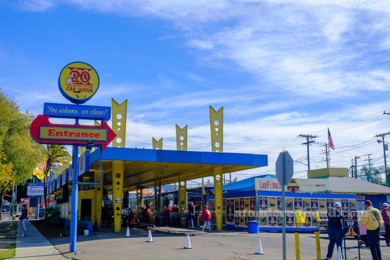 Cars exit the car wash, which features a blue roof and a yellow posts.