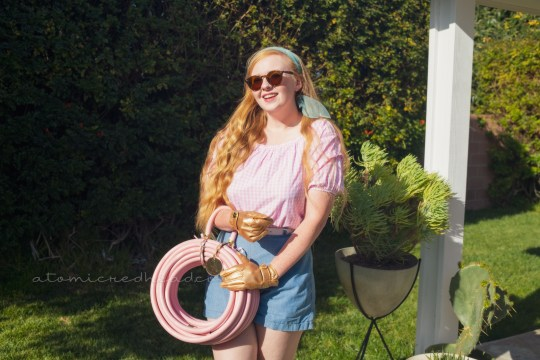 Myself, standing in our backyard, wearing a pink and white gingham peasant top, blue shorts, gold gardening gloves, holding a pink garden hose that is curled up with a handle.