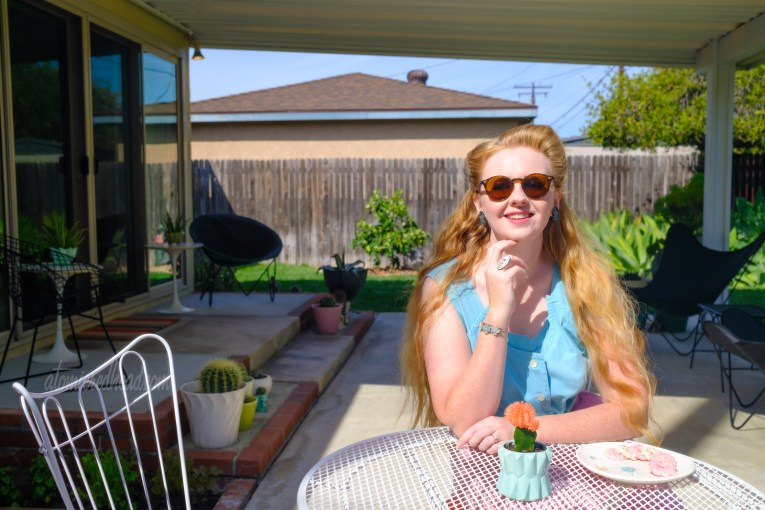 Myself, wearing a turquoise sleeveless top, seated at a white metal table. A small cacti sits in a turquoise planter in the middle of the table, a plate with pink and white cookies sits nearby.