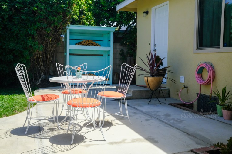 View of the white patio table and chairs with their orange cushions. Bullet shaped planters sit near the backdoor, and a turquoise wood shed stands behind.