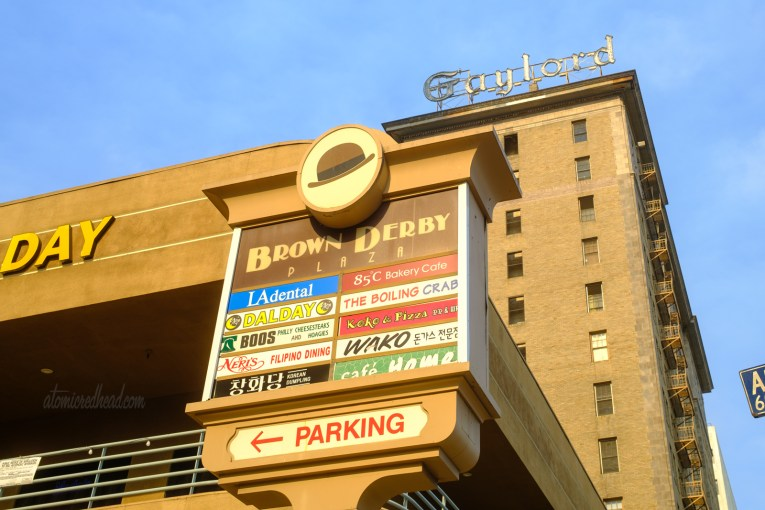 """Sign for Brown Derby Plaza. At the top is a small image of a brown bowler hat and text below reads """"Brown Derby Plaza"""" signs for other businesses are below, and include a bakery, dentist, and Korean food."""
