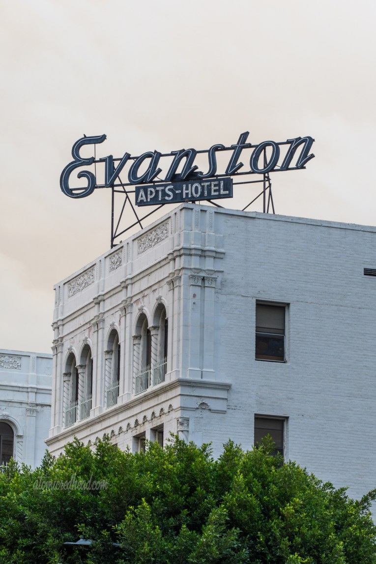 """An Italianate designed apartment building painted white. Atop the roof in elegant script reads """"Evanston"""" with a smaller sign below reading """"Apts Hotel"""""""