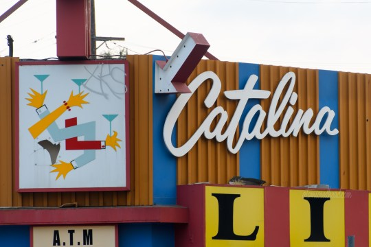 The signage for Catalina Liquor, all of which is backlit plastic. Above the door is a sign that is an abstract of various arms intertwined holding martini glasses.