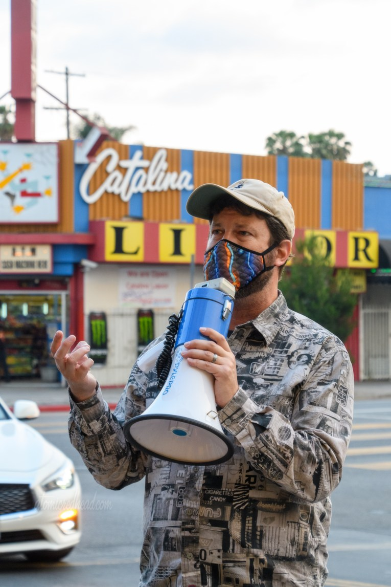 Eric uses a megaphone to talk to those of us on the tour, he wears a shirt made of black and white images of neon signs, behind him is Catalina Liquor.