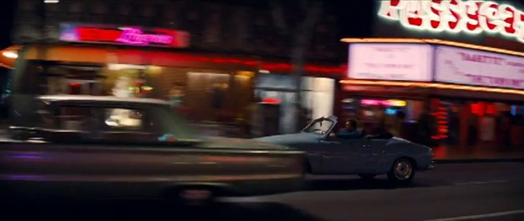 Cliff speeds down Hollywood Boulevard in his blue Garmin Gia, the plastic back lit sign of the Pussycat Theater is visible, with funky, bubbly letters spelling out its name.