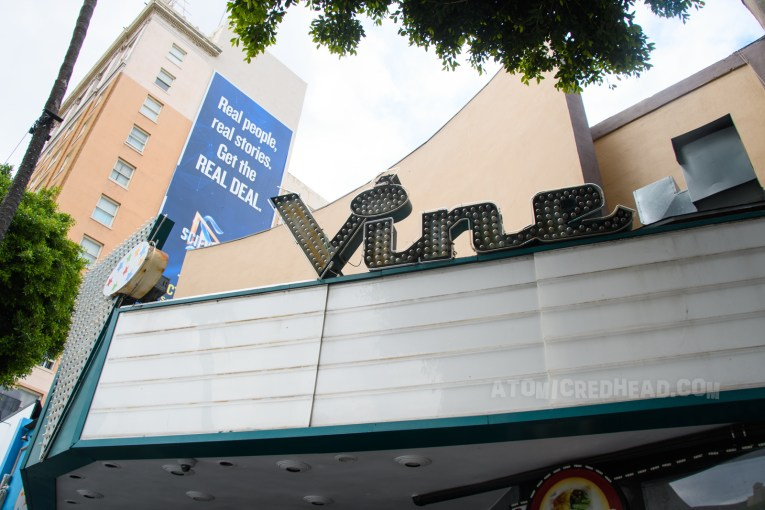 """Marquee for the Vine theater. Script reads """"Vine"""" with bulbs that would illuminate. A large V faces the street from the front of the marquee."""