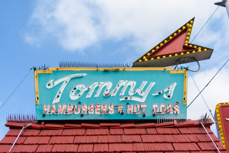 """Close-up of the neon sign atop the shack's red roof reading """"Tommy's Hamburgers & Hot Dogs"""""""