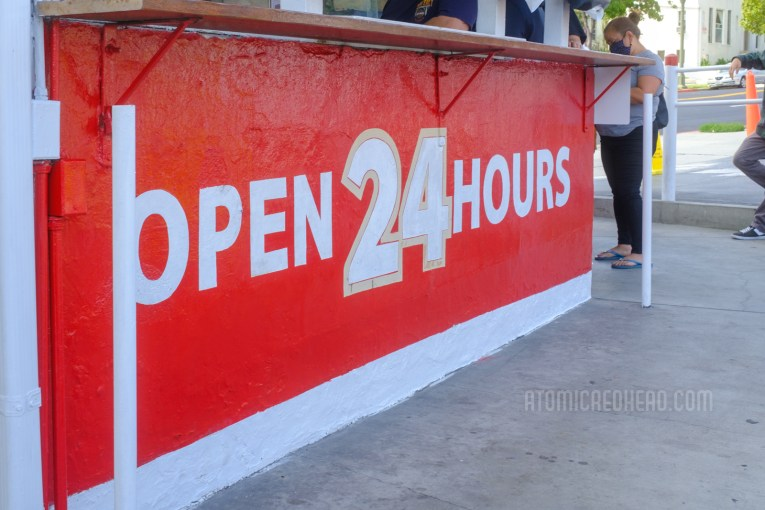 """""""Open 24 Hours"""" painted in red and white on the side of the original shack."""