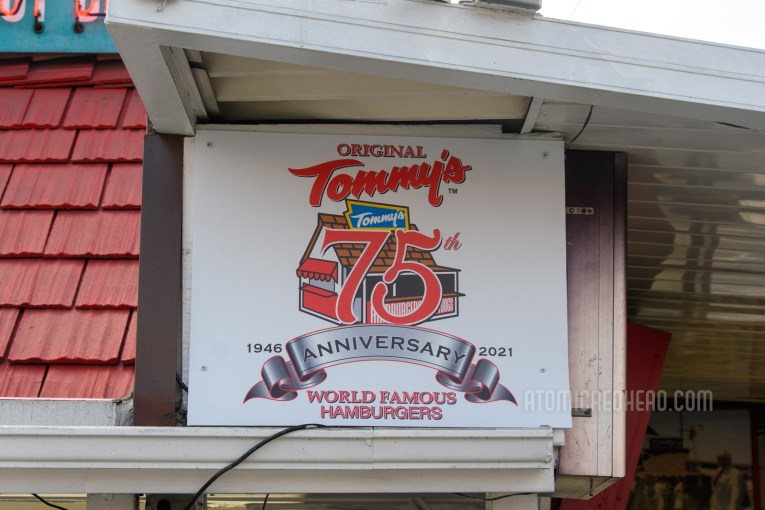 """Sign celebrating 75 years. An illustration of the small original shack with text overlay reading """"Original Tommy's 75th Anniversary 1946-2021 World Famous Hamburgers"""""""