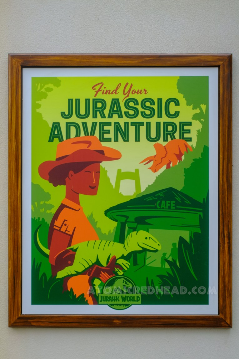 """Poster for Jurassic World, which features an illustration of a Jurassic World employee holding a small dinosaur, the cafe building is off in the distance. Text reads """"Find Your Jurassic Adventure"""""""