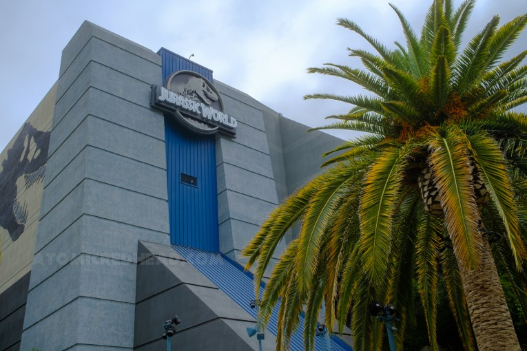 The Jurassic World building, which is grey and blue, and features the Jurassic World logo of a T-Rex skeleton.