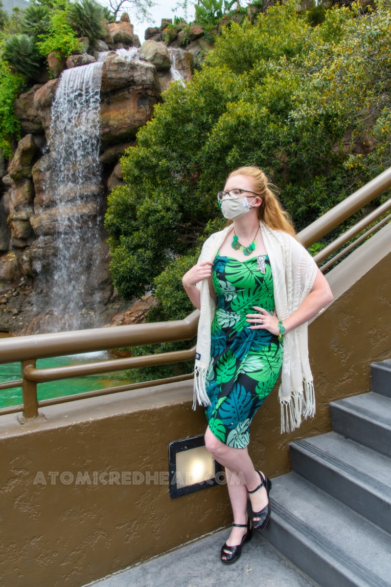 Myself standing in front of the water feature of the Jurassic World ride, wearing a dress featuring a tropical leaf and frond design, with a necklace and bracelet that also features leaves and fronds, a white shawl is wrapped around my shoulders.